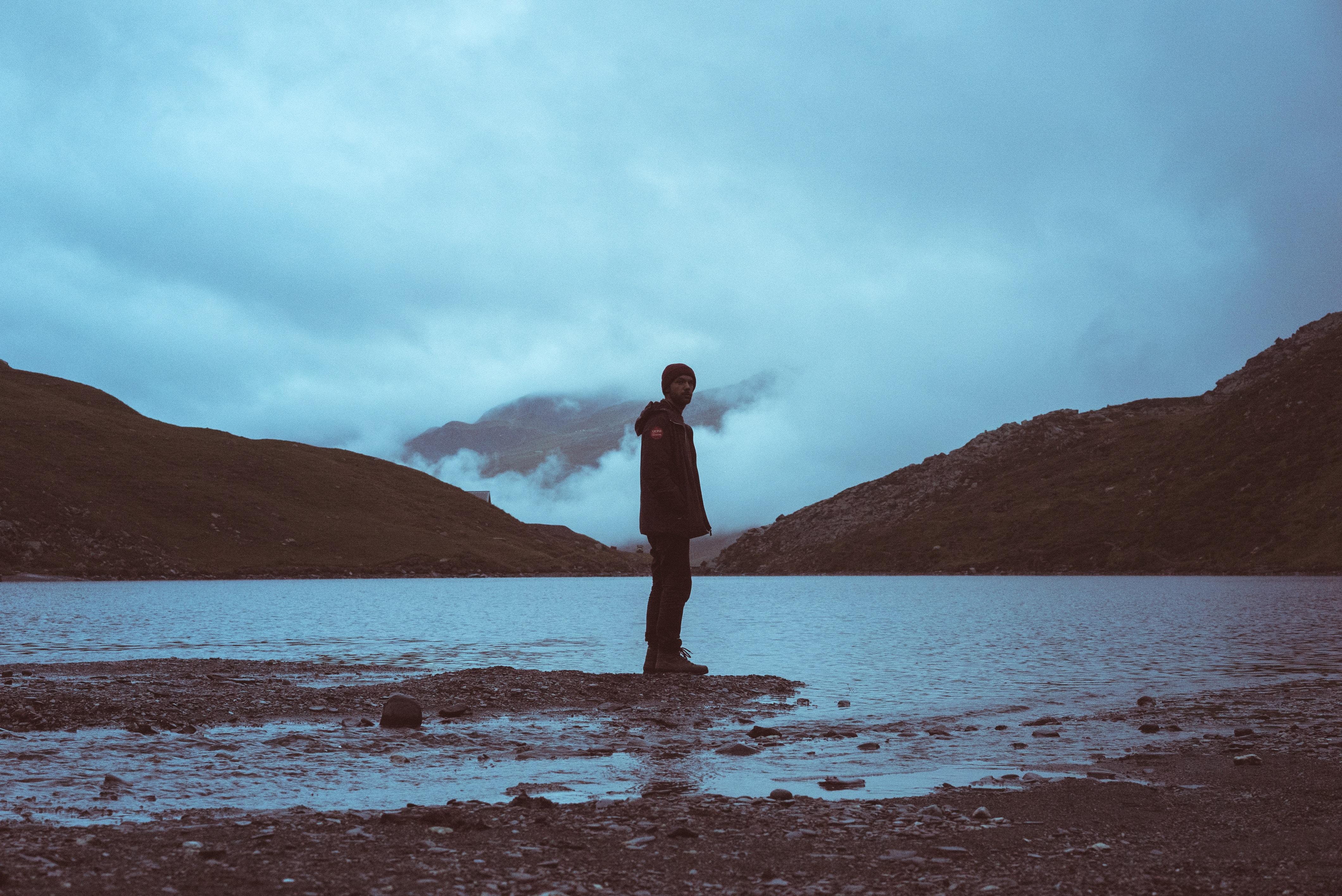 man standing on shoreline