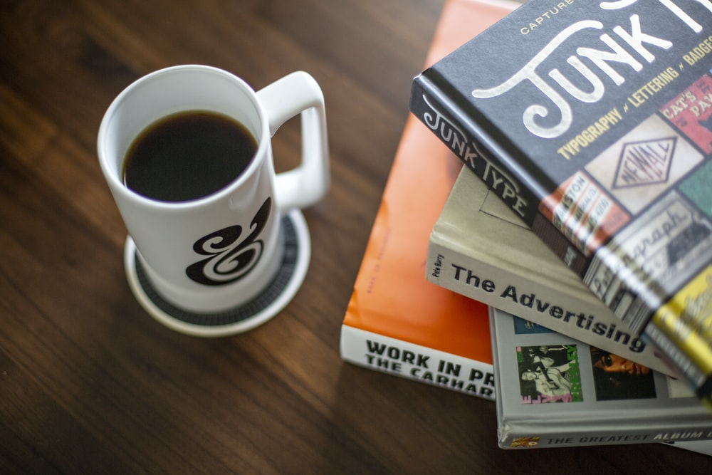 white and black coffee mug near pile of books on brown wooden surface