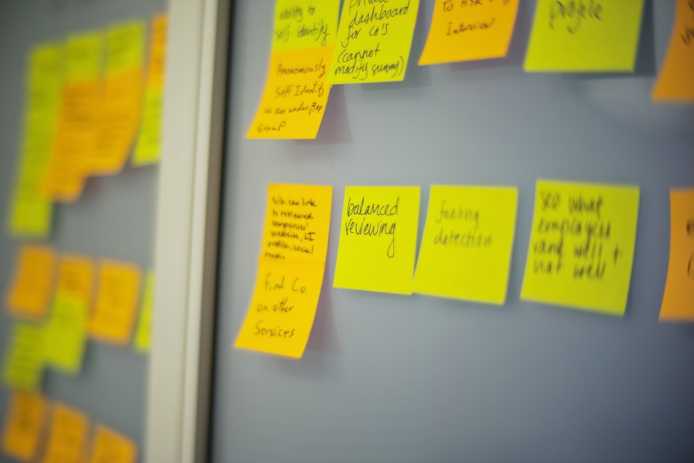 selective focus photography of yellow and orange post-it notes on wall