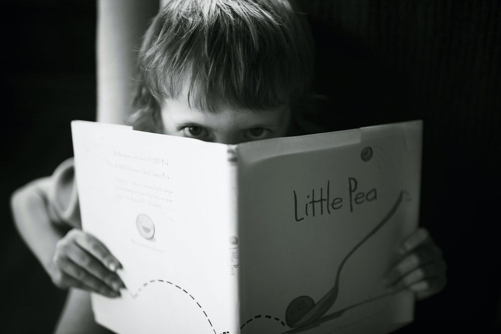 grayscale photo of boy holding book