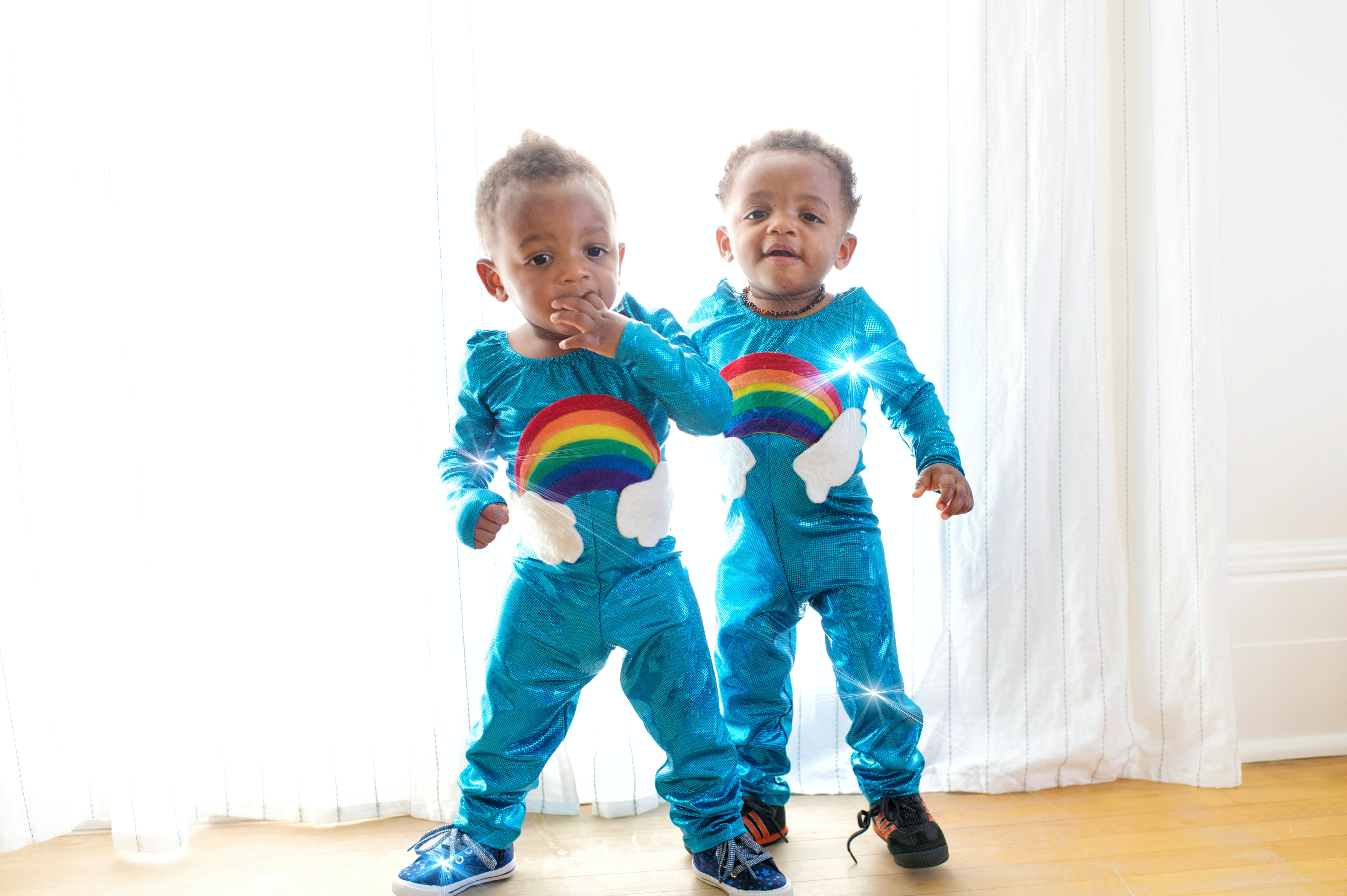 two toddler's standing in front of white window curtain