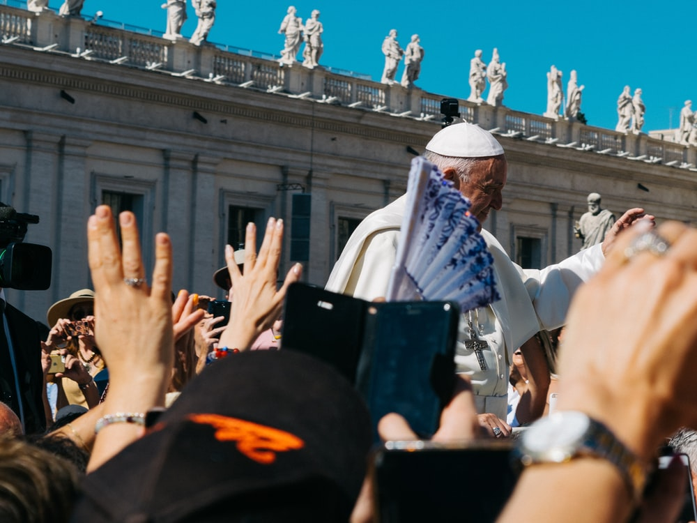 Pope surrounded with people during daytime