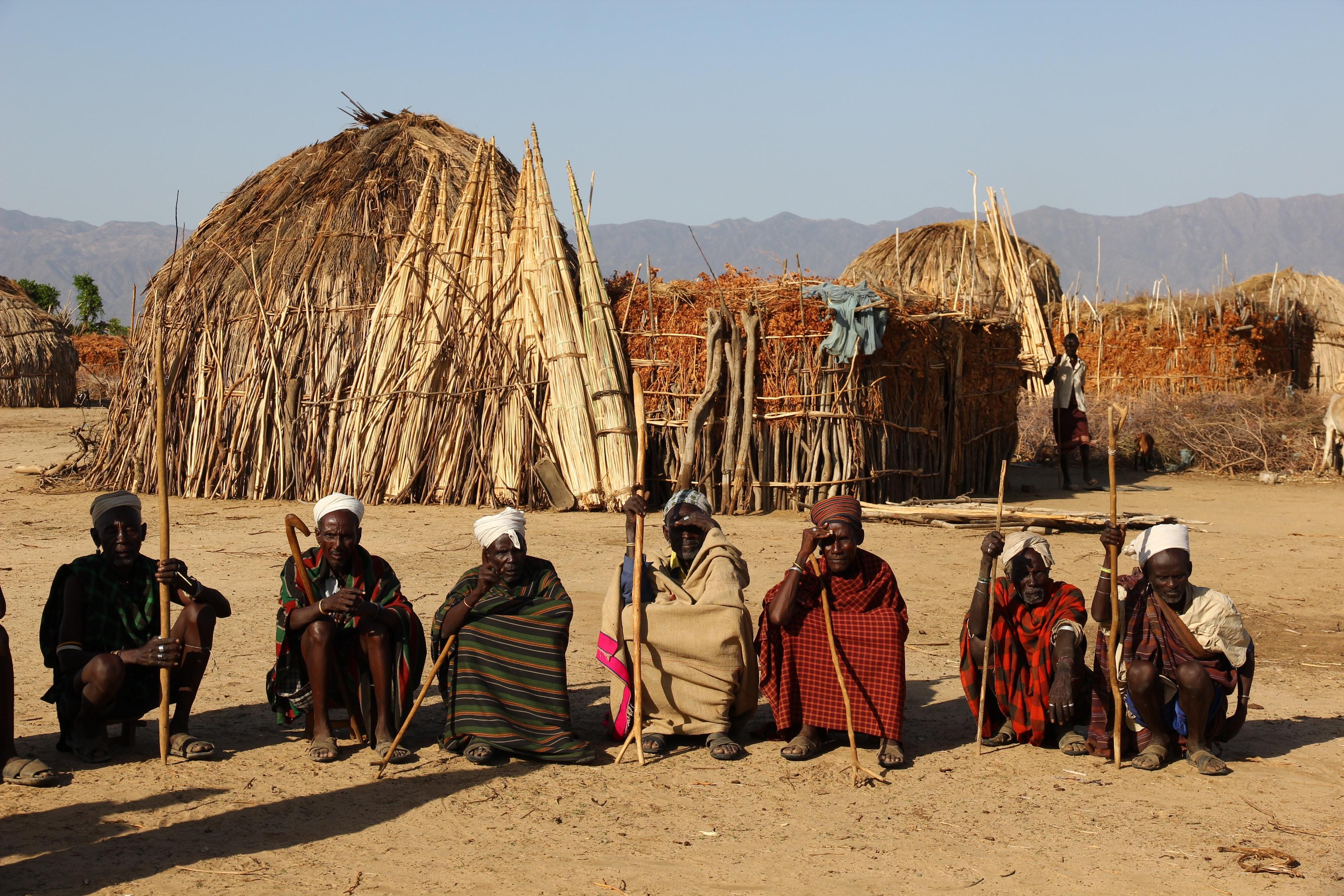 group of tribal men sitting on soil while holding sticks