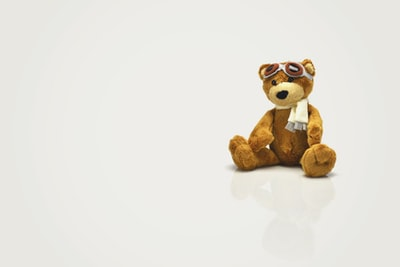 brown bear plush toy on white surface toy zoom background