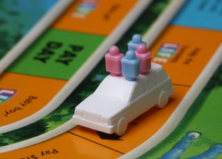 white and blue car toy on top of orange game board