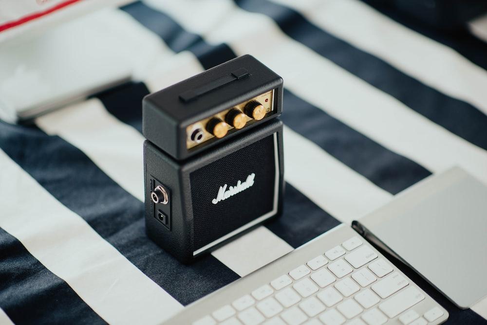 black Marshall portable speaker near white computer keyboard on black and white striped textile