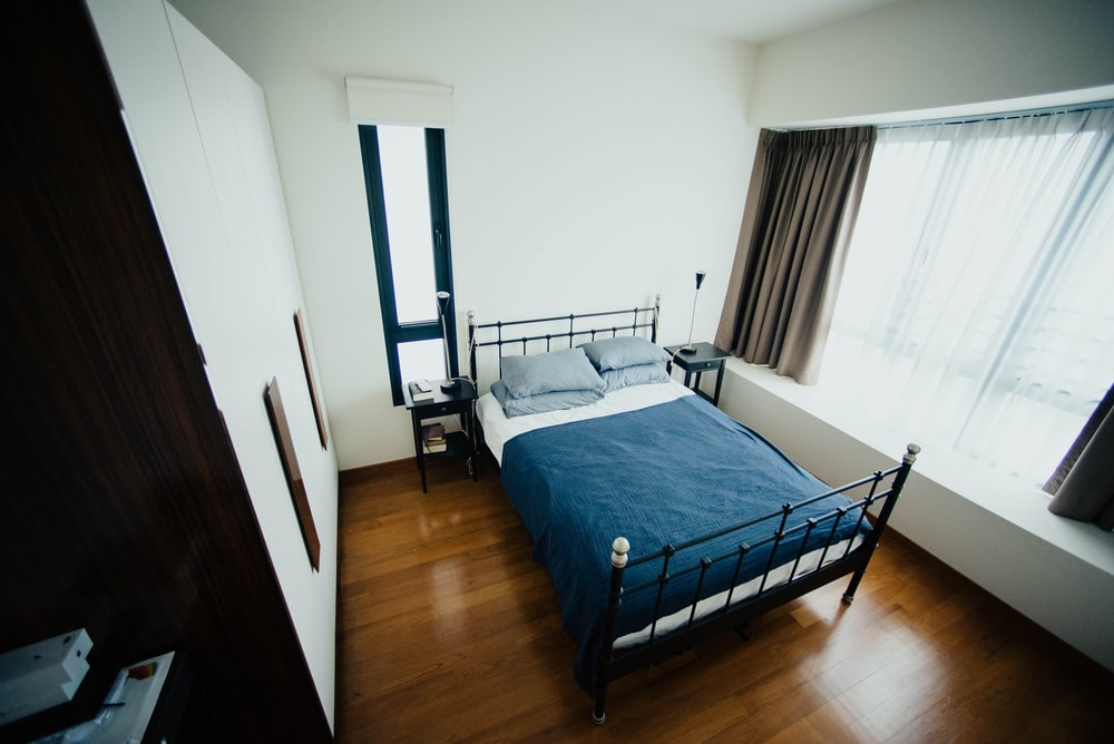blue and white bed sheet and black bed frame in room