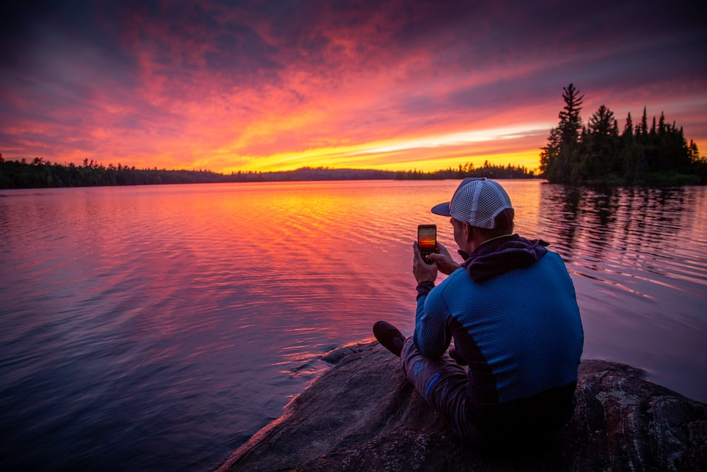 man sitting on gray rock while taking photo of silhouette
