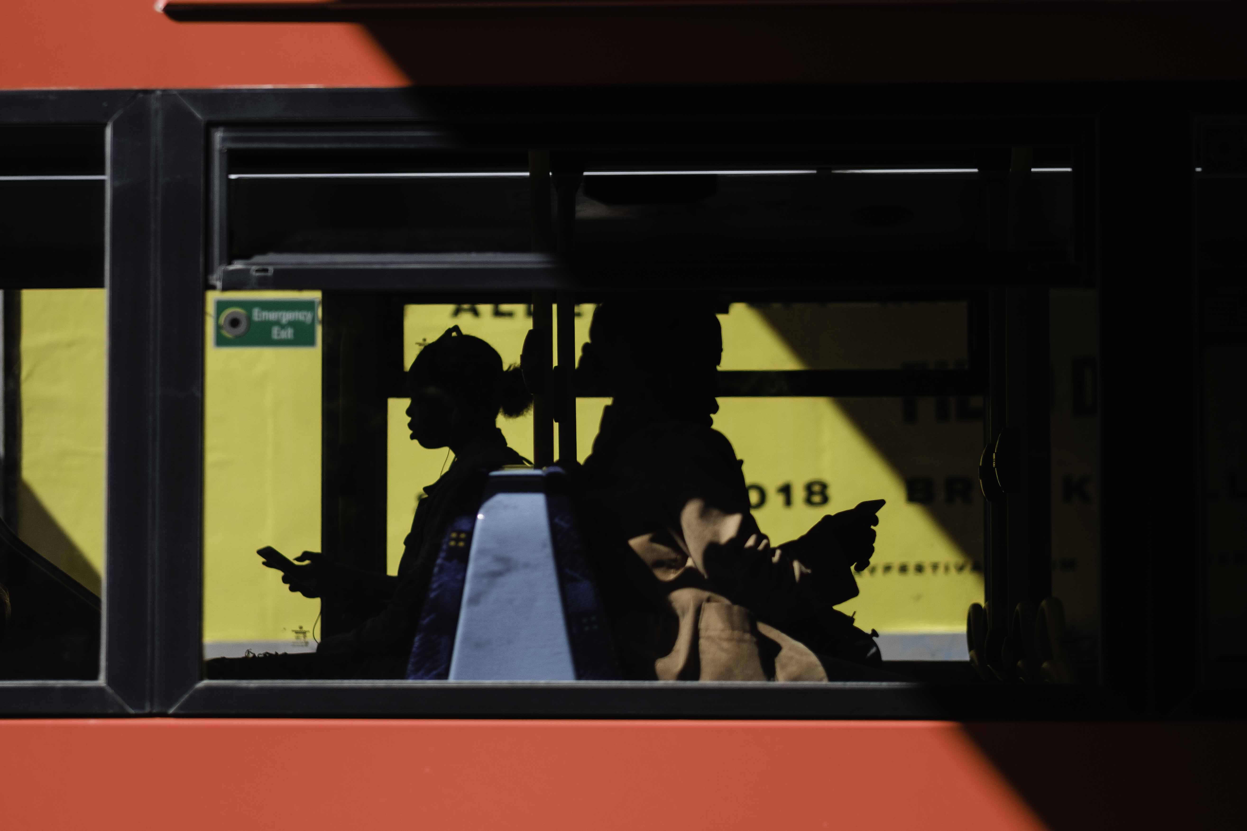 people inside bus sitting while using smartphone