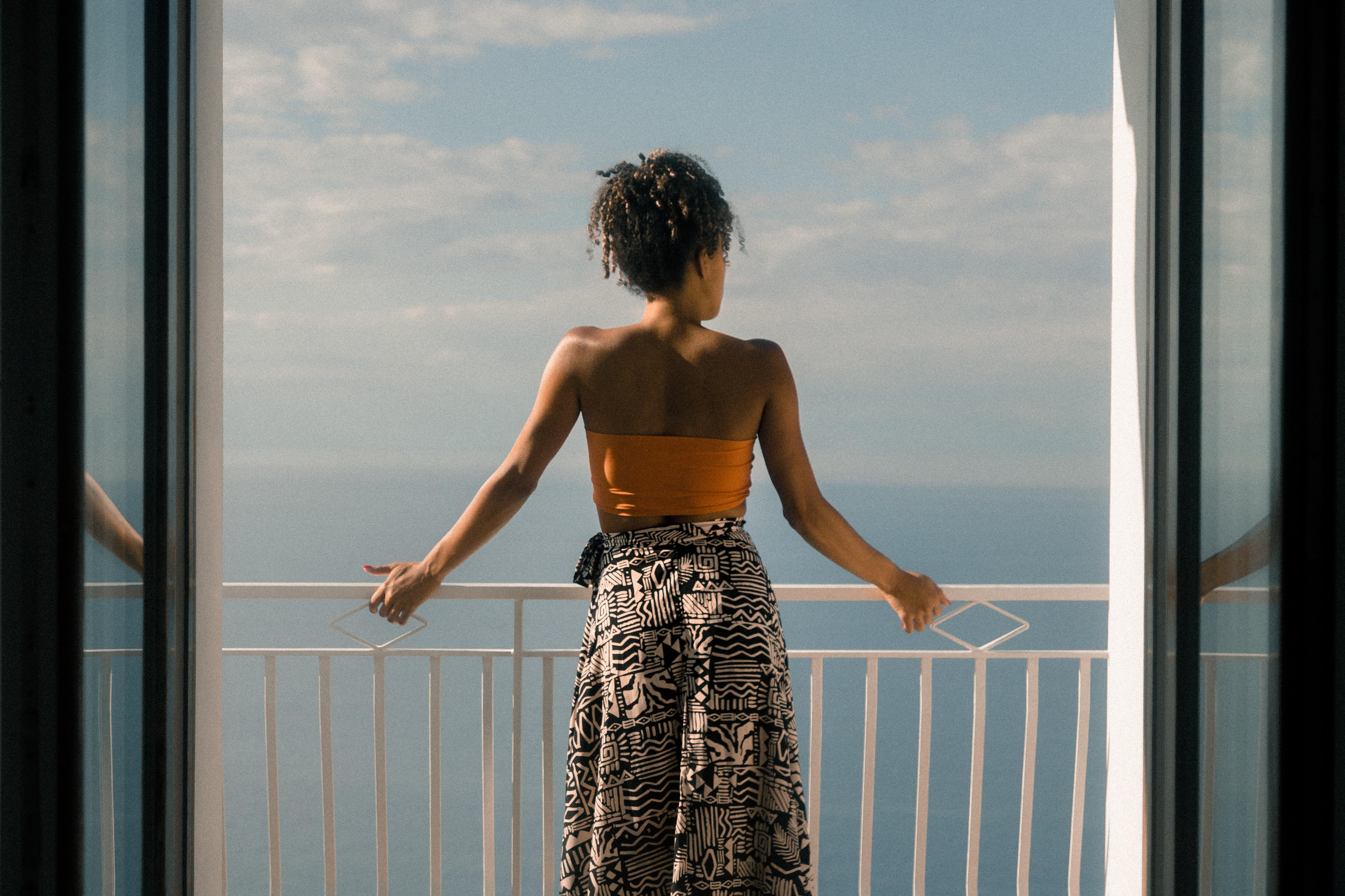 woman wearing orange tube and black skirt facing terrace