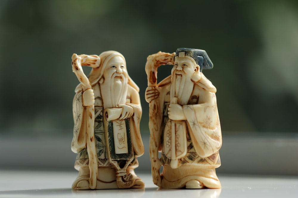 person taking photo of ceramic figurines on table