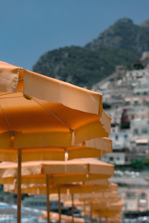 aligned orange patio umbrellas near mountain
