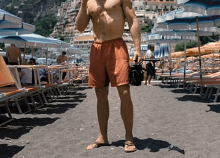 man wearing orange shorts standing on beach sand while drinking on cup