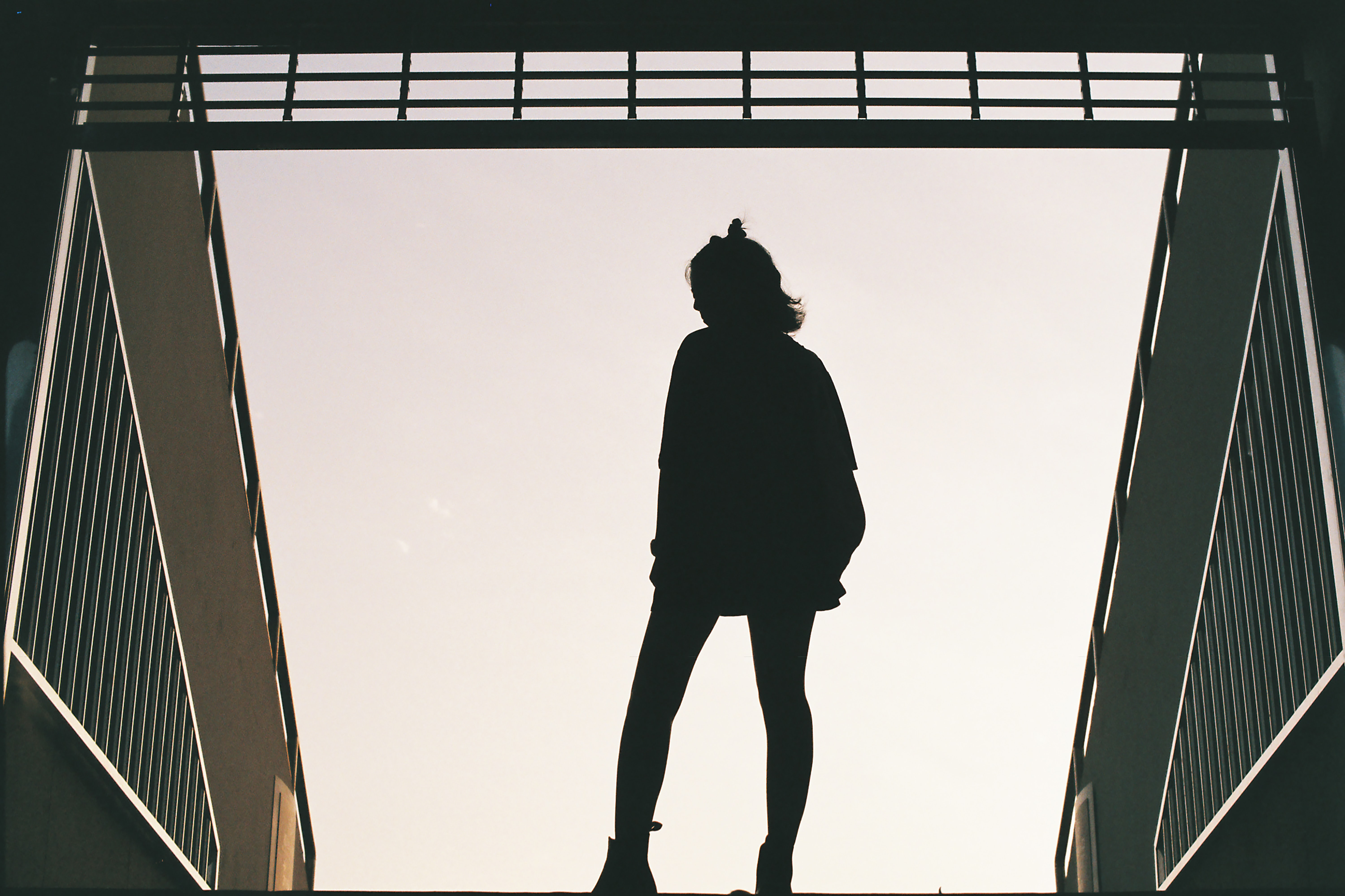 silhouette photo of woman standing on concrete road