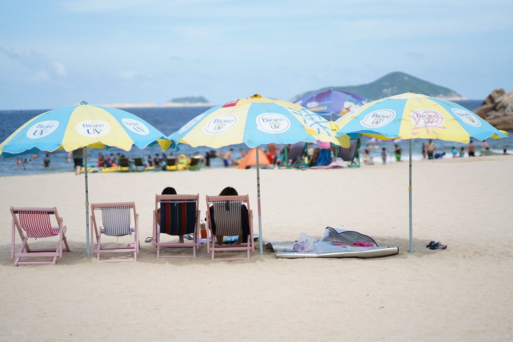 two person relaxing on sun chair near seashore