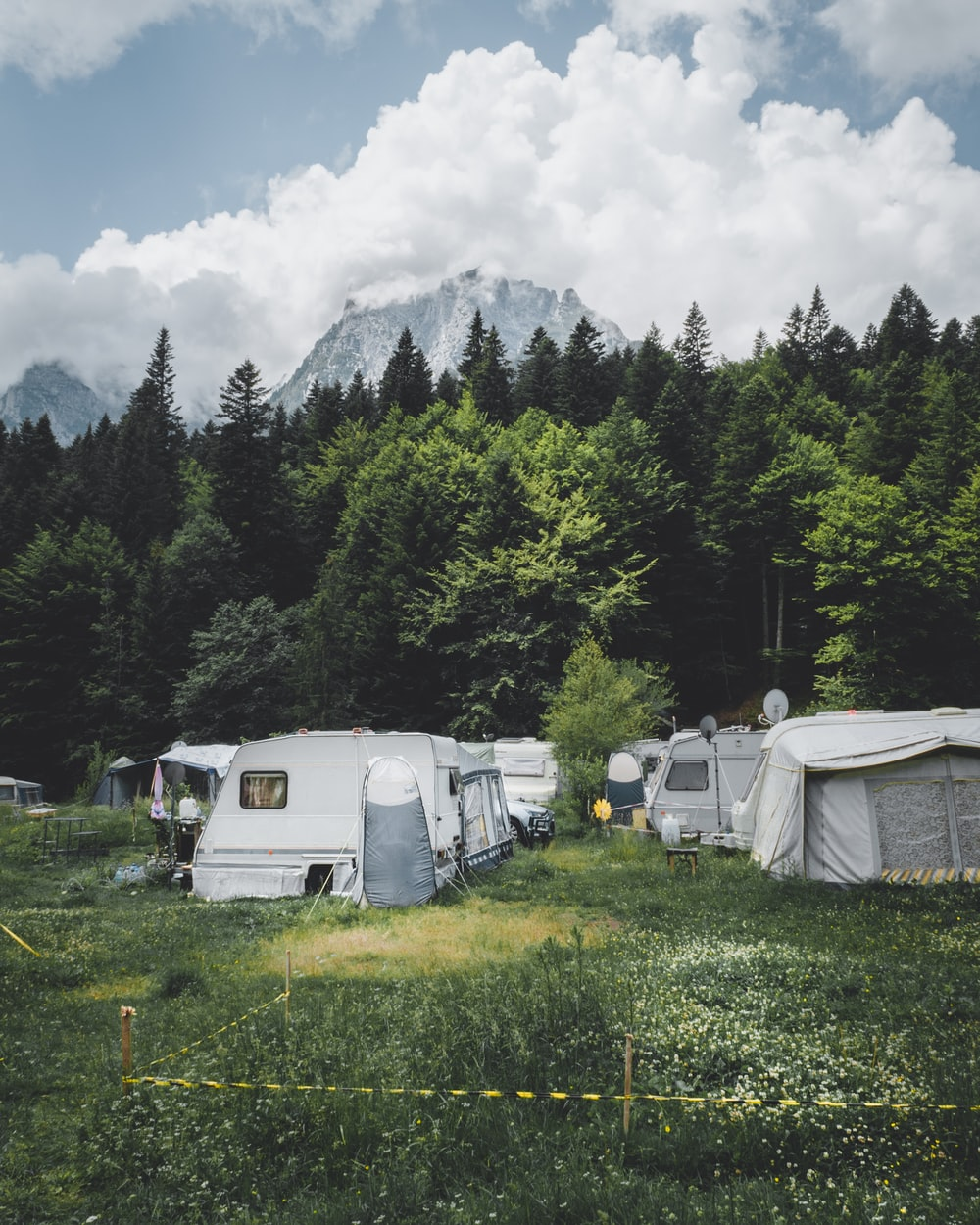 camper trailer near trees with snow-capped mountain at distance