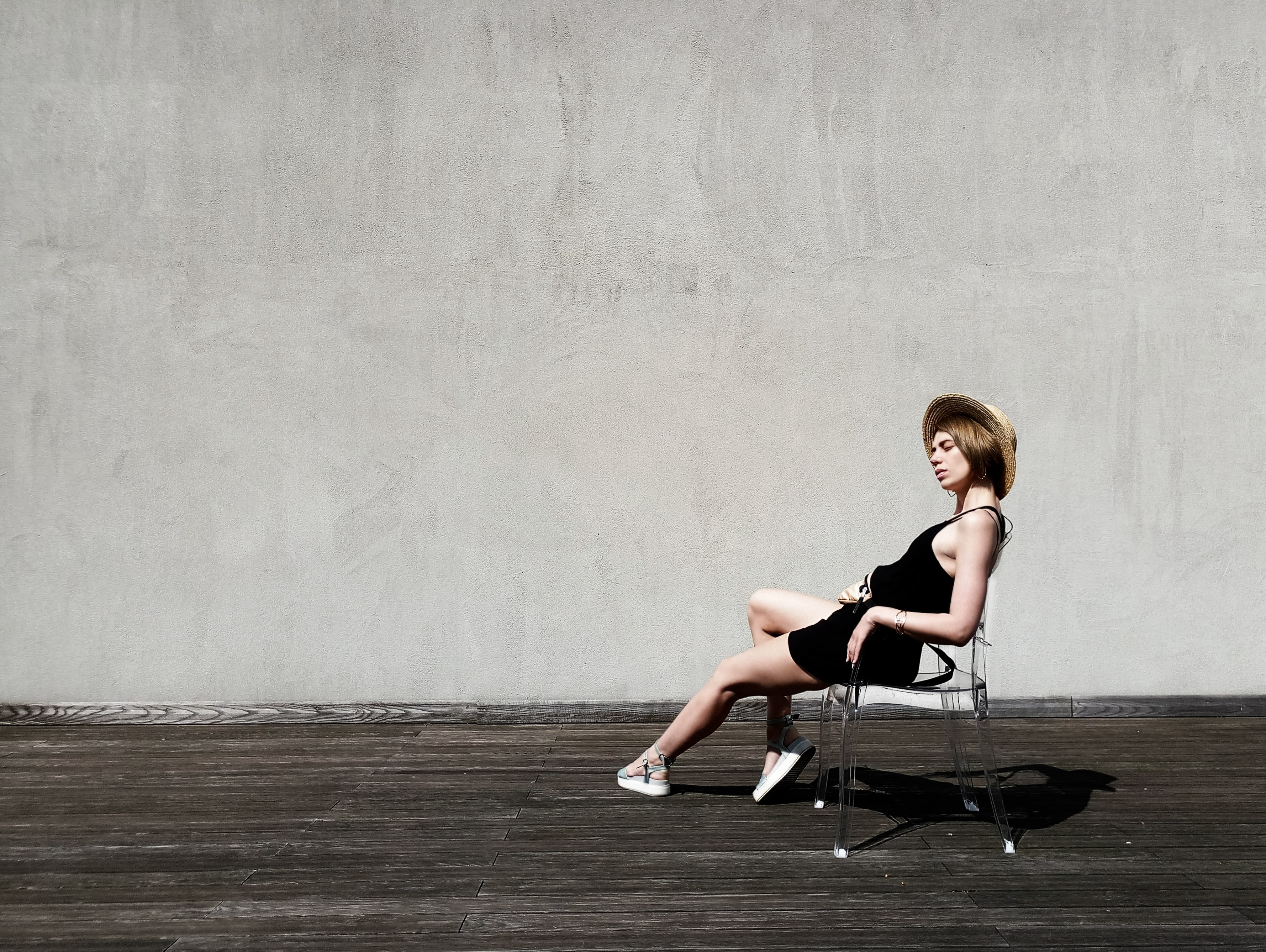 woman sitting on black armchair near gray wall
