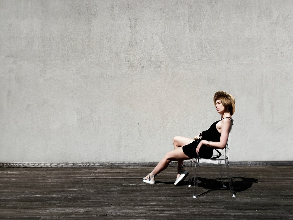 woman sitting on black armchair near gray wall