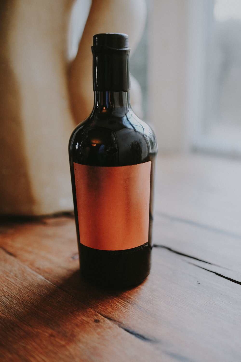 brown glass bottle on wooden surface