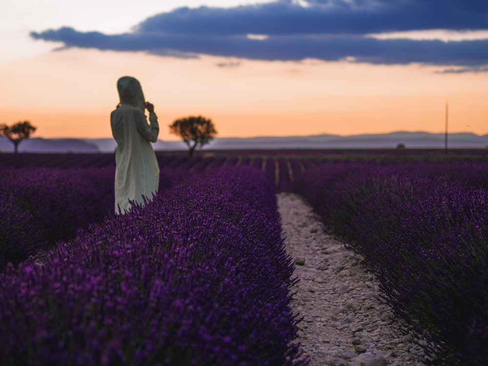 woman standing in front of the purple flowers