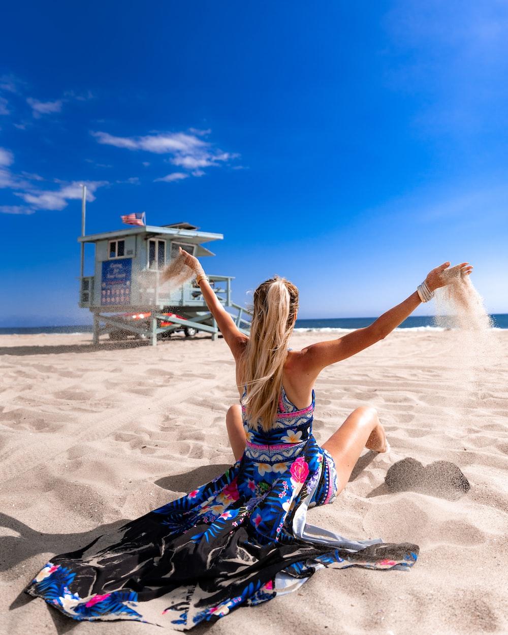 woman sitting on beach sand