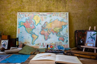 world map poster near book and easel world zoom background