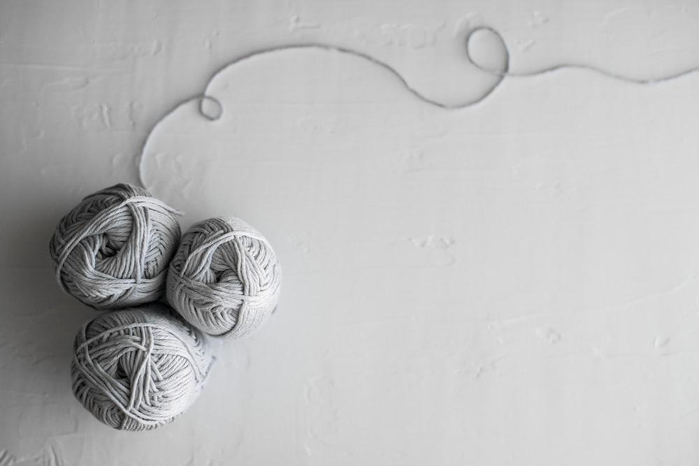 flat lay photography of three white yarn balls