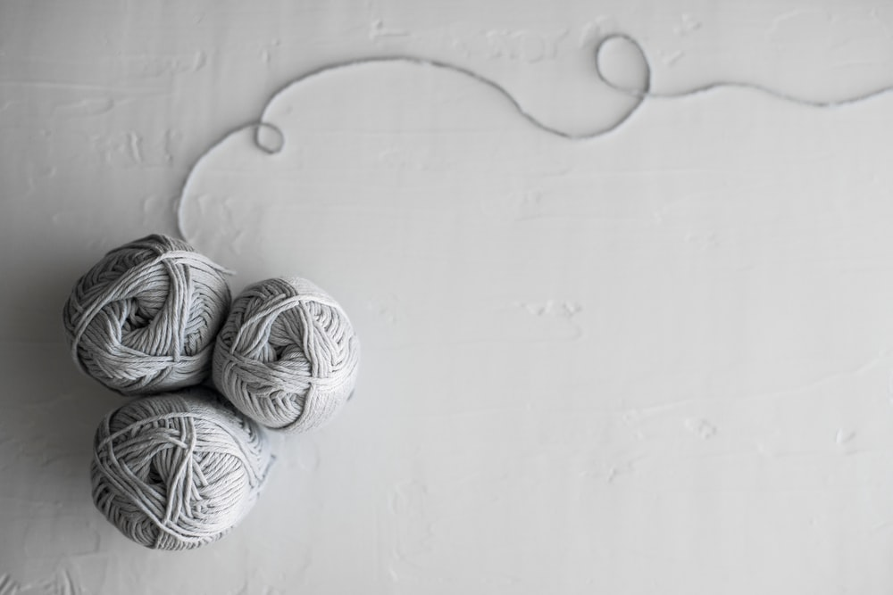 flat lay photography of three white yarn balls