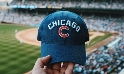 Chicago person holding blue Chicago Cubs cap