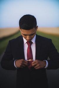 man holding red necktie