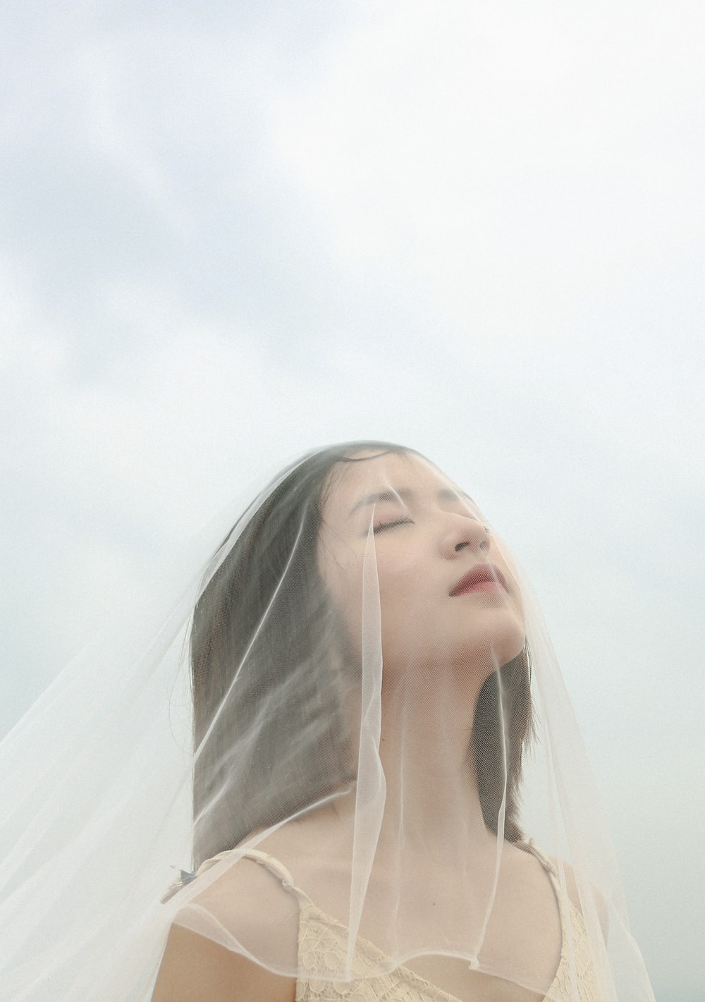 woman wearing veil under cloudy sky