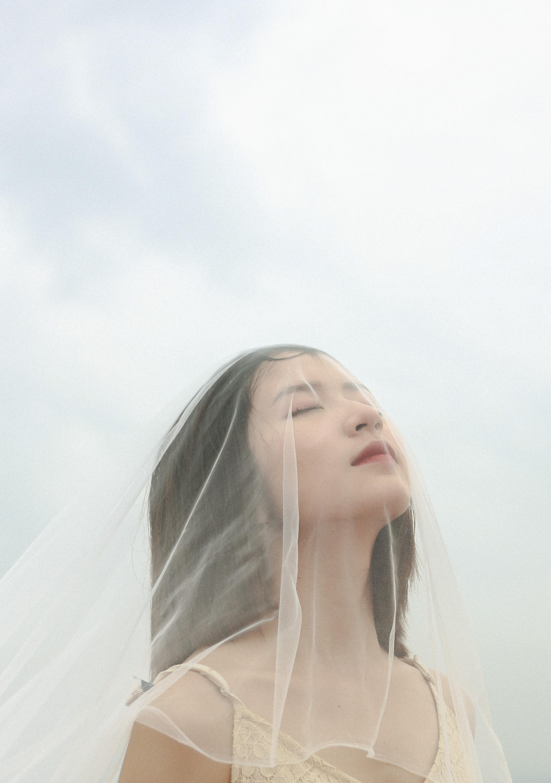 woman wearing veil under cloudy sky