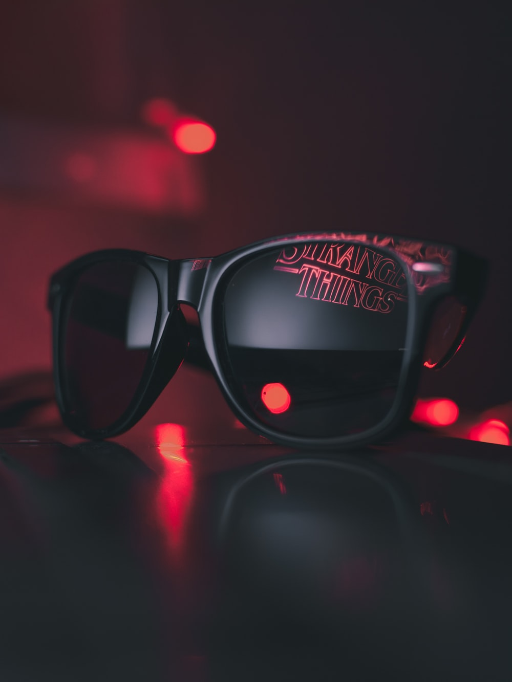black wayfarer sunglasses on black surface