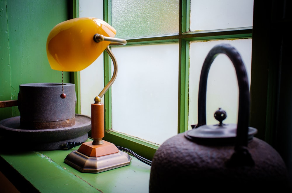 orange bankers lamp near to glass window
