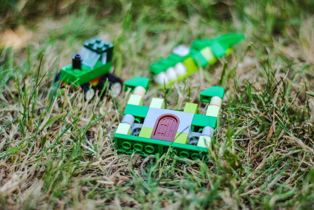 green and white plastic Lego castle toy on green grass