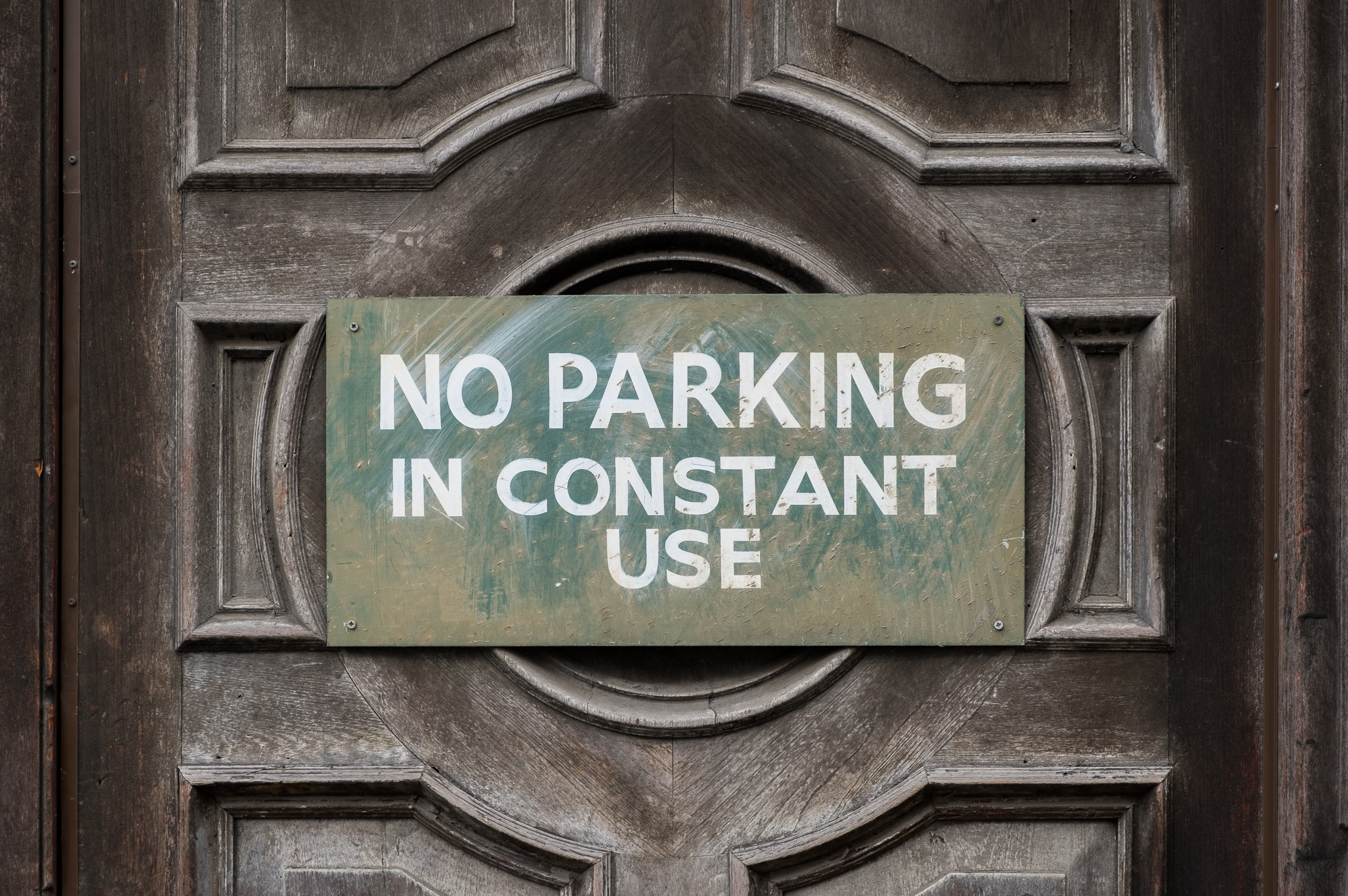 no parking in constant use signboard hung on door