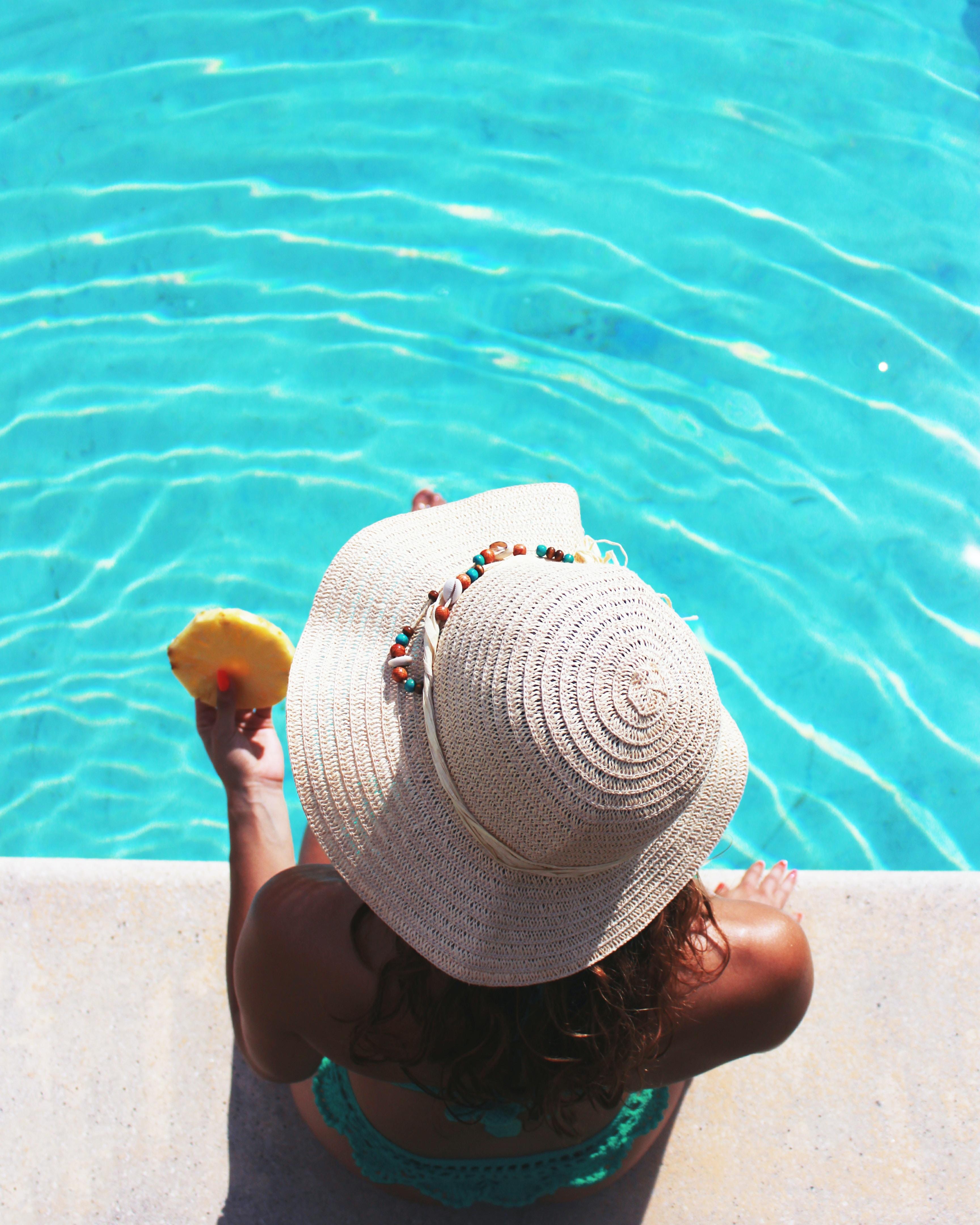woman sitting beside swimming pool