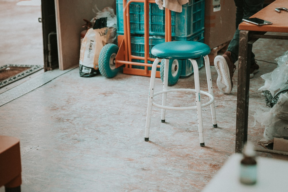 empty round green stools beside brown table