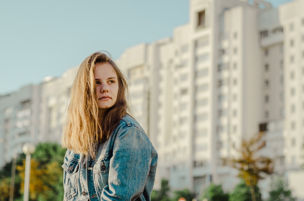woman wearing blue denim jacket standing in front of white concrete buildings