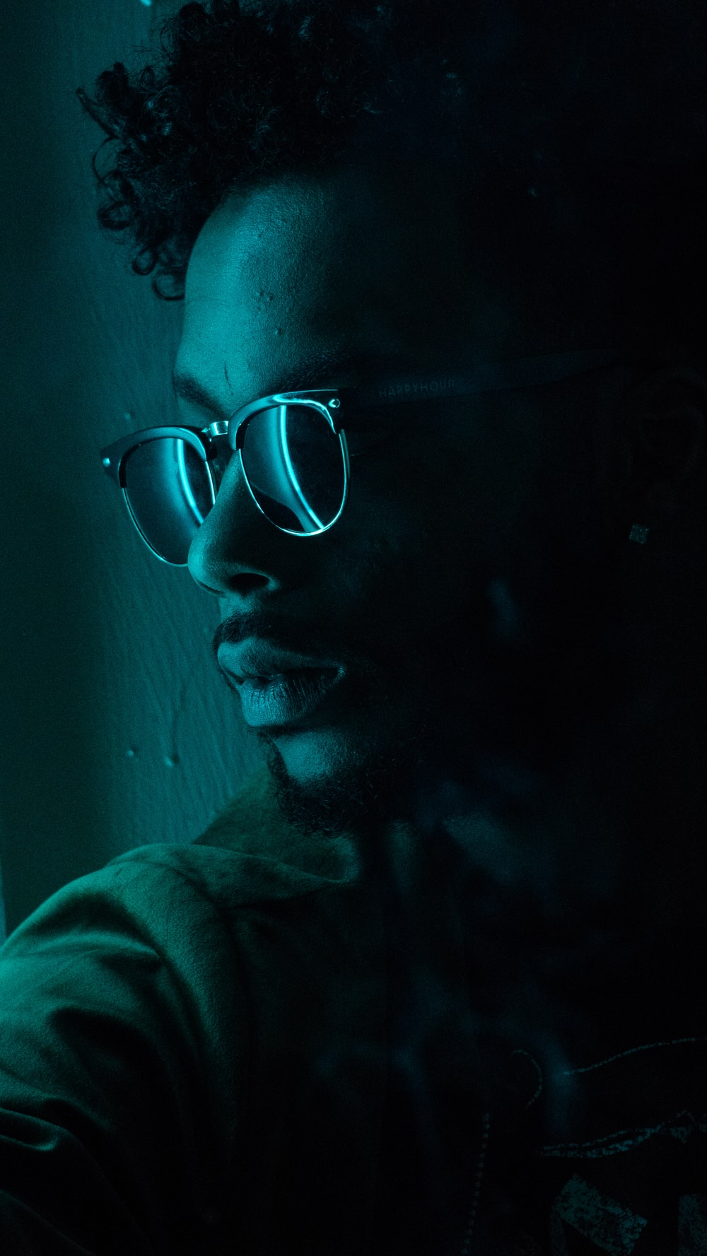 man sitting near wall wearing black framed sunglasses