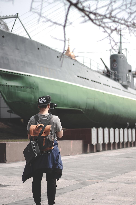 man standing taking photo of ship