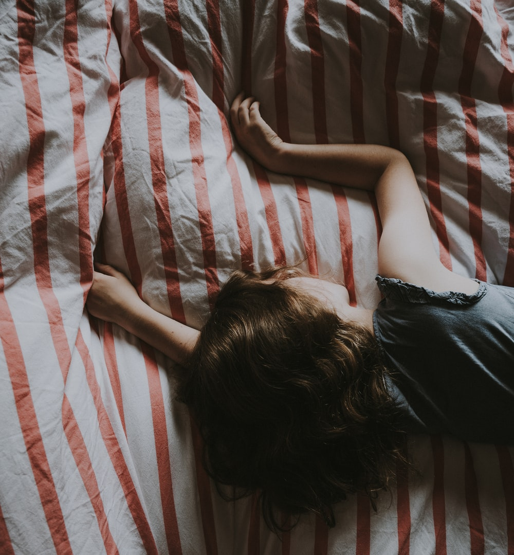 woman laying on white and red striped bedspread