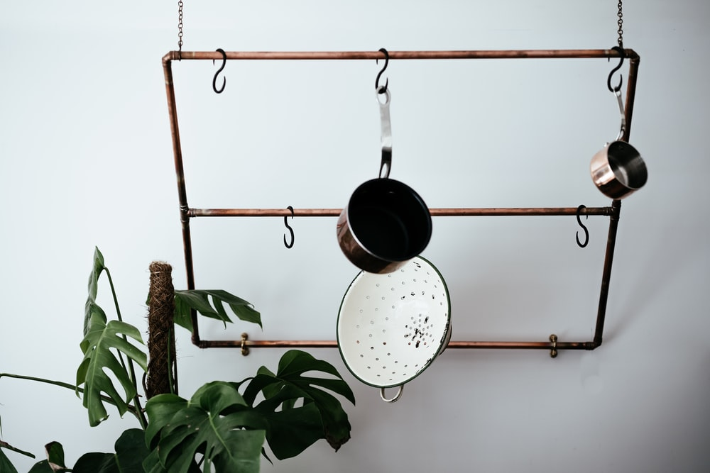 brass-colored pot rack near white wall and plant