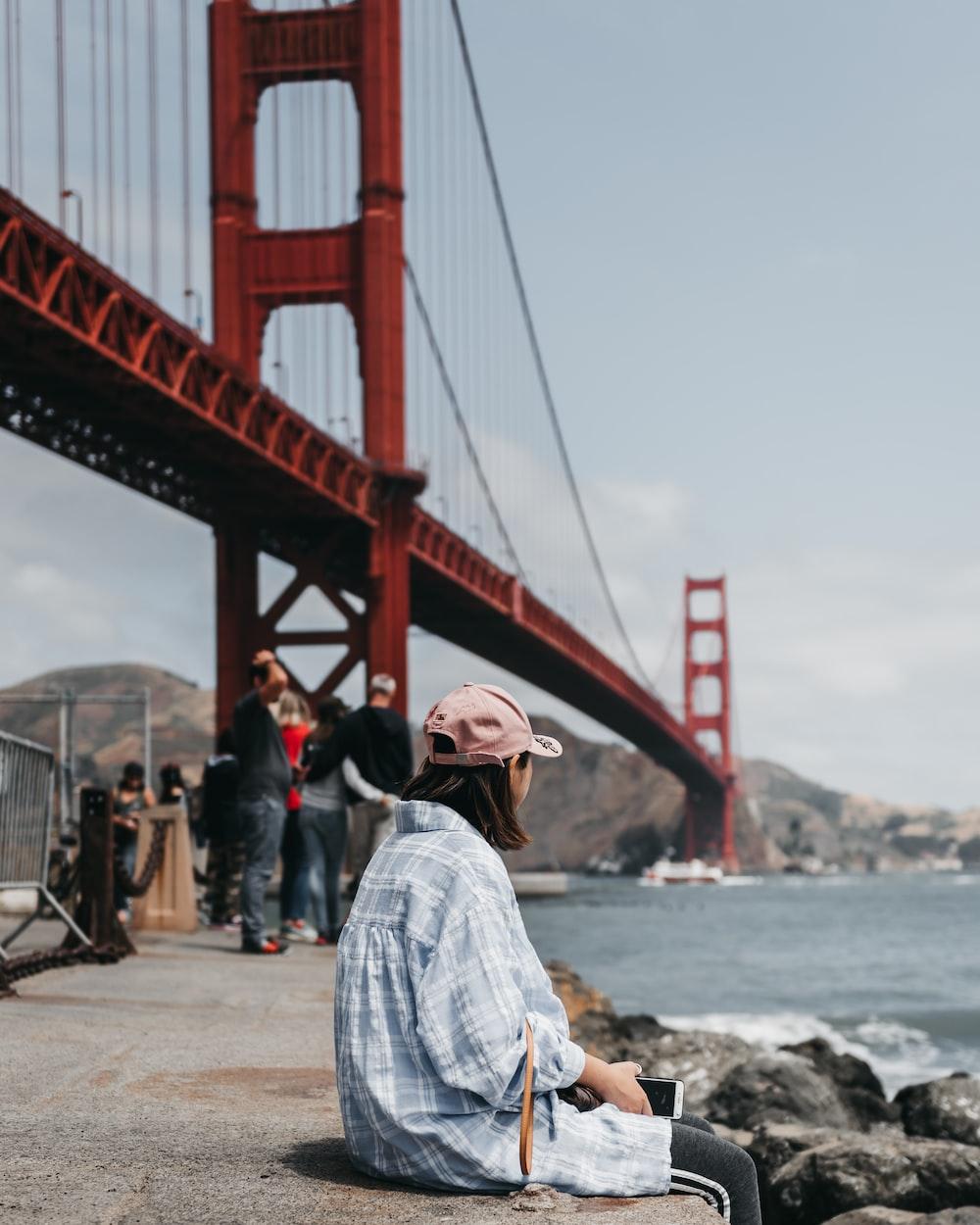 woman sitting on concrete floor near Golden Gate Bridge,