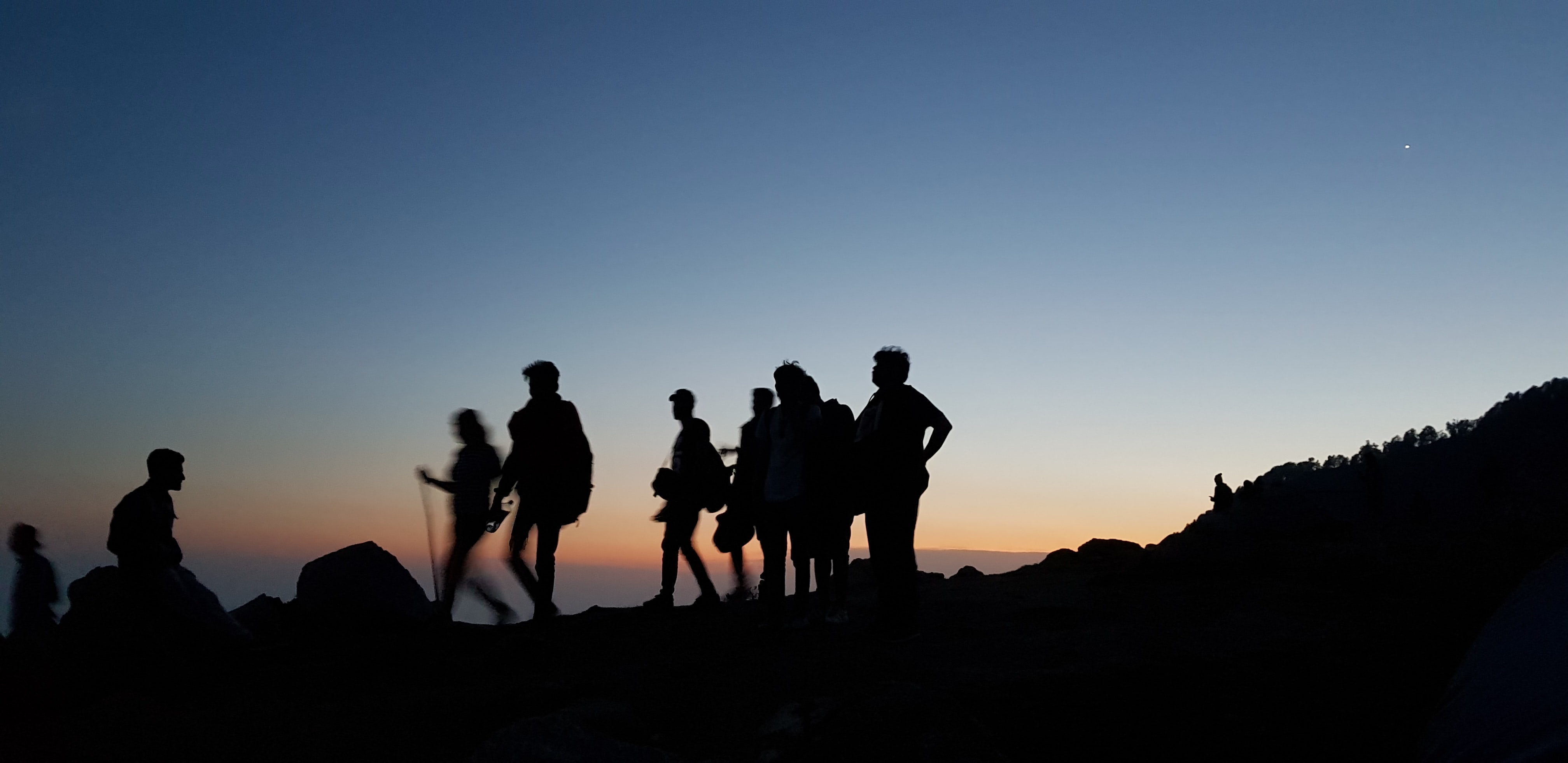 silhouette on people standing on mountain during blue hour