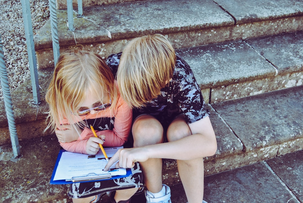 boy and girl answering questions on white paper