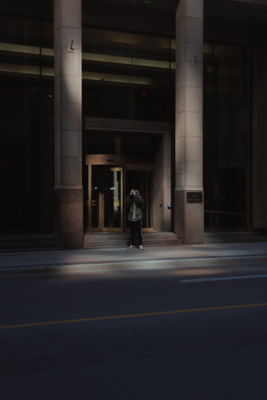 person standing near gray concrete building