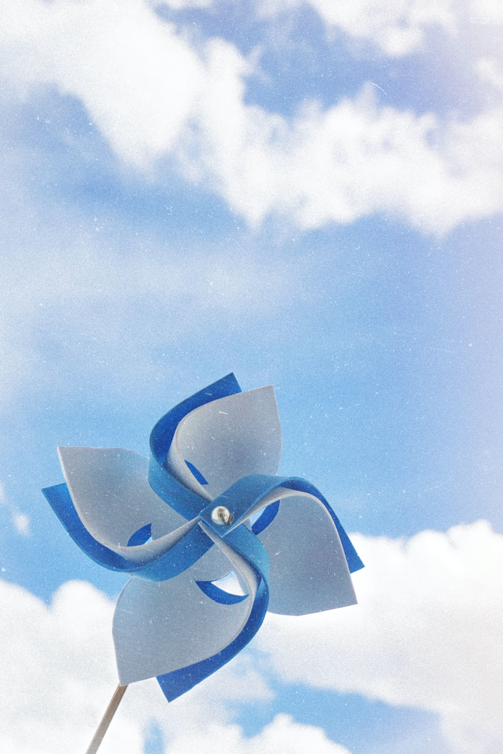 white and blue handheld windmill under cloudy skies