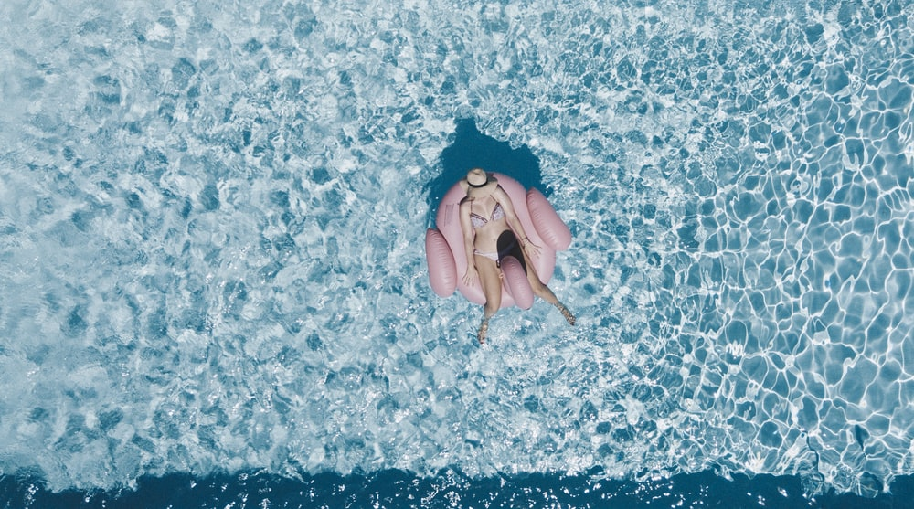 woman on pink buoy surrounded by body of water during daytime