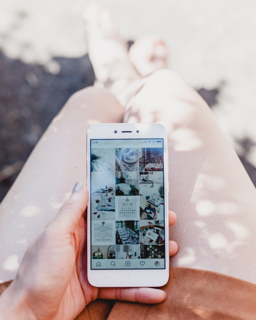 person holding white smartphone showing Instagram feed